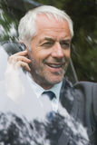 Happy mature businessman on the phone driving Royalty Free Stock Photo