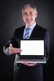Happy Mature Businessman Showing Laptop Stock Images