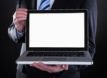 Happy mature businessman showing laptop. Over Black Background royalty free stock photos
