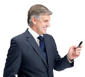 Happy mature businessman texting form his mobile Stock Image