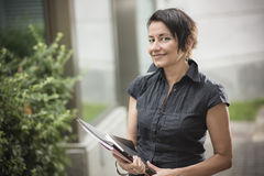 Happy mature businesswoman. Bright portrait of a beautiful mature corporate woman outside her work building stock photography