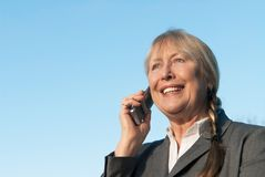 Happy mature businesswoman using cellphone. Royalty Free Stock Photos