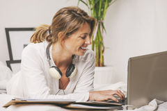 Happy mature businesswoman working with laptop at home. Stock Photos