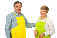 Happy mature couple with aprons Royalty Free Stock Images