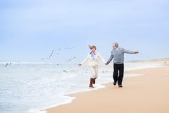 Happy mature couple at beautiful winter beach. Happy mature couple running at a beautiful winter beach with seagulls royalty free stock image