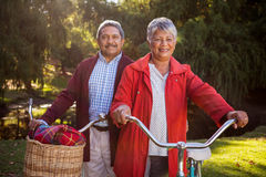 Happy mature couple with bicycle stock photography