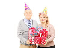 Happy mature couple with birthday hats holding presents Stock Photos