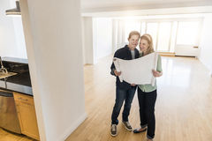 Happy Mature Couple With Blueprint At New Home Stock Photo