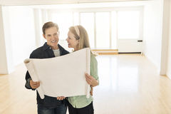 Happy Mature Couple With Blueprint At New Home Stock Image