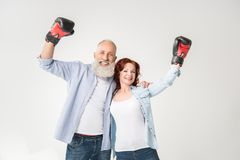 Mature couple in boxing gloves. Happy mature couple in boxing gloves, isolated on white Royalty Free Stock Images