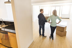 Happy Mature Couple With Cardboard Boxes At New Home Stock Photo