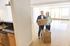 Happy Mature Couple With Cardboard Boxes At New Home Stock Photos