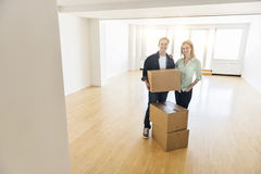 Happy Mature Couple With Cardboard Boxes In New House Stock Photos