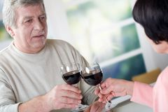 A happy mature couple celebrating their years together with red. Wine Royalty Free Stock Image