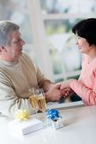 A happy mature couple celebrating their years together with red Stock Photos