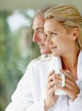 Happy mature couple with coffee cups looking away Stock Photos