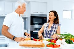 Married couple cooking at home. Happy mature couple cooking together at home stock image