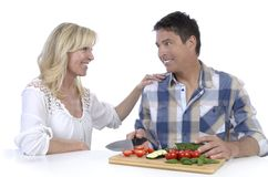 Happy mature couple cutting vegetables Stock Photo