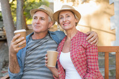Happy mature couple drinking coffee on a bench in the city Royalty Free Stock Photo