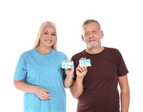 Happy mature couple with driving licenses. On white background stock photography