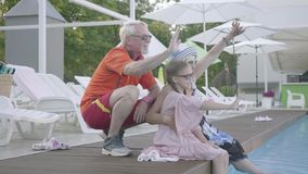 Happy mature couple on the edge of the pool hugging little granddaughter. Grandmother, grandfather and grandchild waving. Happy mature couple on the edge of the stock footage