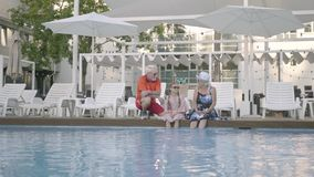 Happy mature couple with little granddaughter on the edge of the luxury pool. Grandmother, grandfather and grandchild. Happy mature couple on the edge of the stock footage