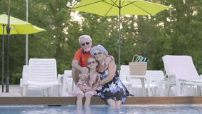 Portrait mature couple hugging little granddaughter on the edge of the pool. Grandmother, grandfather and grandchild. Happy mature couple on the edge of the pool stock video