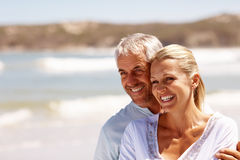 Happy mature couple embracing at the beach. Happy mature couple embracing on a sunny day at the beach Stock Photo