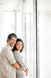 Happy mature couple embracing near a window Royalty Free Stock Photos