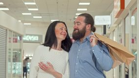 Happy mature couple enjoying seasonal sale at local shopping mall stock footage