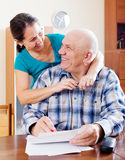 Happy  mature couple fills in paper Stock Photos