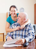 Happy mature couple fills in paper questionnaire Royalty Free Stock Image