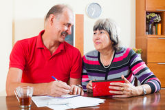 Happy mature couple with financial documents. In home royalty free stock images
