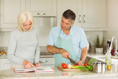 Happy mature couple following a vegetarian recipe Royalty Free Stock Images