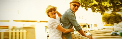 Happy mature couple going for a bike ride in the city. On a sunny day Stock Image