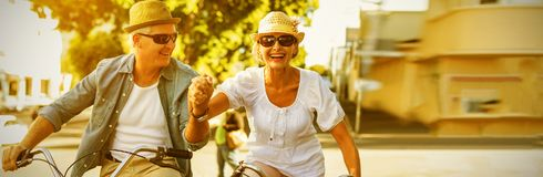 Happy mature couple going for a bike ride in the city. On a sunny day Royalty Free Stock Image