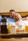 Happy mature couple having breakfast in bed Stock Photo