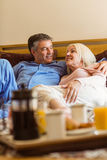Happy mature couple having breakfast in bed Stock Images