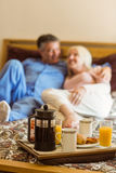 Happy mature couple having breakfast in bed Royalty Free Stock Image