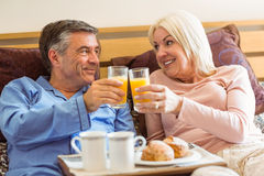 Happy mature couple having breakfast in bed Royalty Free Stock Photos