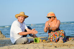 Happy mature couple having fun sitting at seashore on sandy beach Stock Photo