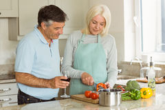 Happy mature couple having red wine while making dinner Stock Image