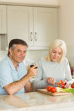 Happy mature couple having red wine while making dinner Stock Photography