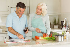 Happy mature couple having red wine while making dinner Stock Photos
