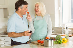 Happy mature couple having red wine while making dinner Royalty Free Stock Images