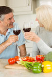 Happy mature couple having red wine while making dinner Stock Photo