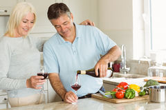Happy mature couple having red wine while making dinner Royalty Free Stock Photo