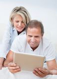 Happy mature couple looking at digital tablet Royalty Free Stock Photos