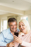 Happy mature couple looking at smartphone together Royalty Free Stock Image