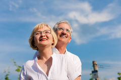 Happy mature couple looking to the blue sky. Happy mature couple - senior people (man and woman) already retired - looking to the blue sky in summer Stock Photos